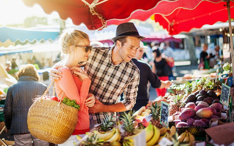 couple looking at produce at open market